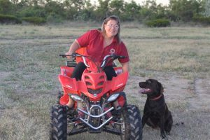 Manager Michelle doing a dawn run on the quad bike with happy four-legged company.